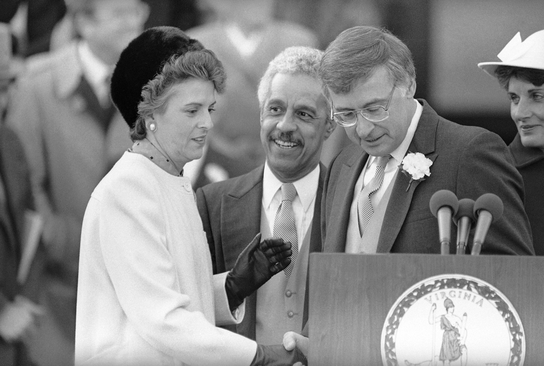 Virginia Governor Gerald Baliles, right, share the podium with Virginia Lt. Governor L. Douglas Wilder, center, and Attorney General Mary Sue Terry, left, after the three were sworn in at the Capitol in Richmond, Virginia on Jan. 11, 1986. (AP Photo/Steve Helber)