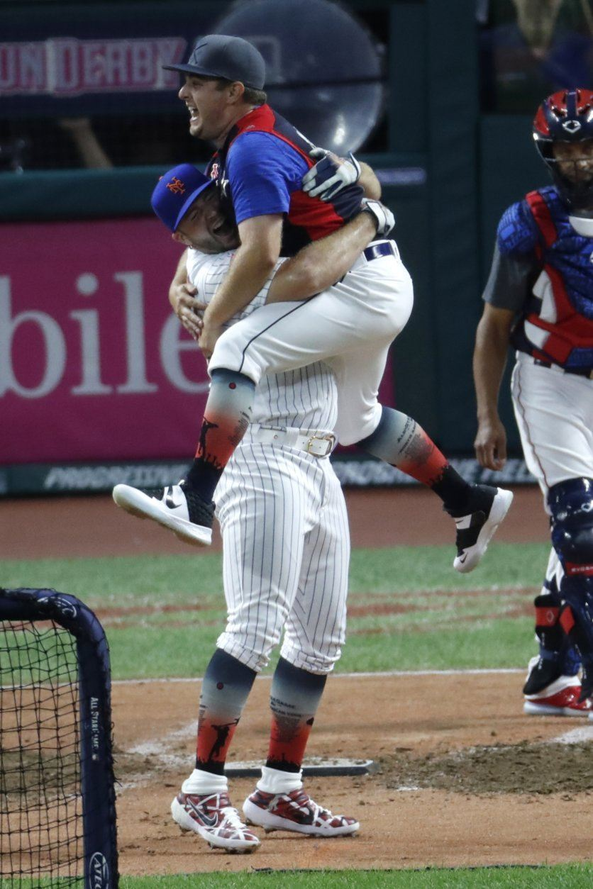 Pete Alonso, of the New York Mets, celebrates with Derek Morgan during the Major League Baseball Home Run Derby, Monday, July 8, 2019, in Cleveland. The MLB baseball All-Star Game will be played Tuesday. (AP Photo/Ron Schwane)