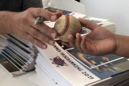 A Nats player autographs a baseball
