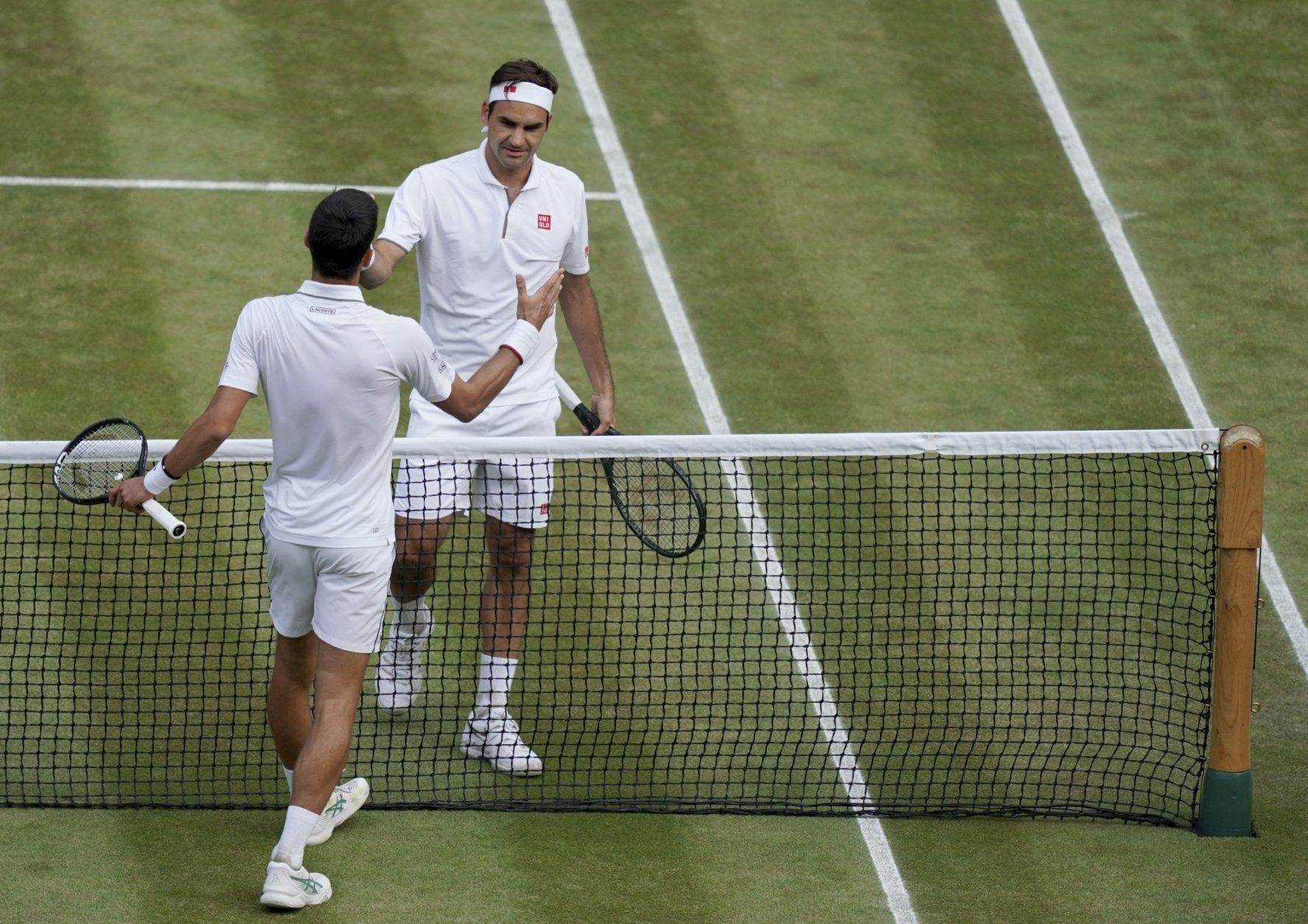 Serbia's Novak Djokovic, left, shakes hands with Switzerland's Roger Federer after he defeats him during the men's singles final match of the Wimbledon Tennis Championships in London, Sunday, July 14, 2019. (Will Oliver/Pool Photo via AP)
