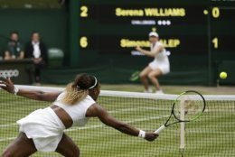 United States' Serena Williams returns the ball to Romania's Simona Halep, background, during the women's singles final match on day twelve of the Wimbledon Tennis Championships in London, Saturday, July 13, 2019.