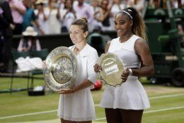 Winner Romania's Simona Halep and second placed United States' Serena Williams, right, pose with their trophies after the women's singles final match on day twelve of the Wimbledon Tennis Championships in London, Saturday, July 13, 2019. (AP Photo/Tim Ireland)