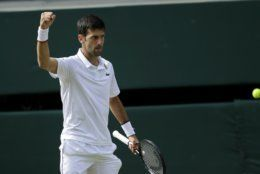 Serbia's Novak Djokovic reacts after scoring a point in the 3rd set tiebreak with Switzerland's Roger Federer during the men's singles final match of the Wimbledon Tennis Championships in London, Sunday, July 14, 2019. (AP Photo/Ben Curtis)