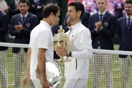 Winner Serbia's Novak Djokovic and second placed Switzerland's Roger Federer, left, hold their trophies after the men's singles final match of the Wimbledon Tennis Championships in London, Sunday, July 14, 2019. (AP Photo/Ben Curtis)