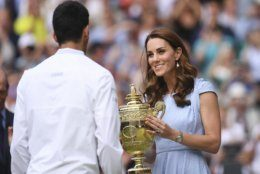 Serbia's Novak Djokovic is presented with the winners trophy by Britain's Kate, Duchess of Cambridge after defeating Switzerland's Roger Federer during the men's singles final match of the Wimbledon Tennis Championships in London, Sunday, July 14, 2019. (Laurence Griffiths/Pool Photo via AP)