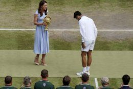 Serbia's Novak Djokovic bows to Britain's Kate, Duchess of Cambridge before being presented with the winners trophy after defeating Switzerland's Roger Federer during the men's singles final match of the Wimbledon Tennis Championships in London, Sunday, July 14, 2019. (Will Oliver/Pool Photo via AP)