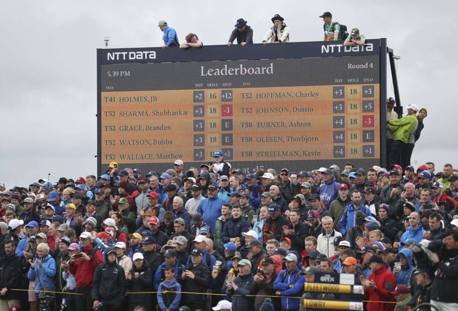Spectators clamber on to and on top of a scoreboard as they vie to get a glimpse of Ireland's Shane Lowry and England's Tommy Fleetwood as they play during the final round of the British Open Golf Championships at Royal Portrush in Northern Ireland, Sunday, July 21, 2019.(AP Photo/Peter Morrison)