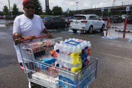 CORRECTS FATHER'S LAST NAME TO WILLIAMS, INSTEAD OF WATKINS - Terrence Williams and his son Kang, 3, load up with water and other supplies in New Orleans, Friday, July 12, 2019, as Tropical Storm Barry threatens. (AP Photo/Kevin McGill)
