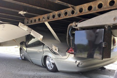 Driver suffers minor injuries when car slides under truck