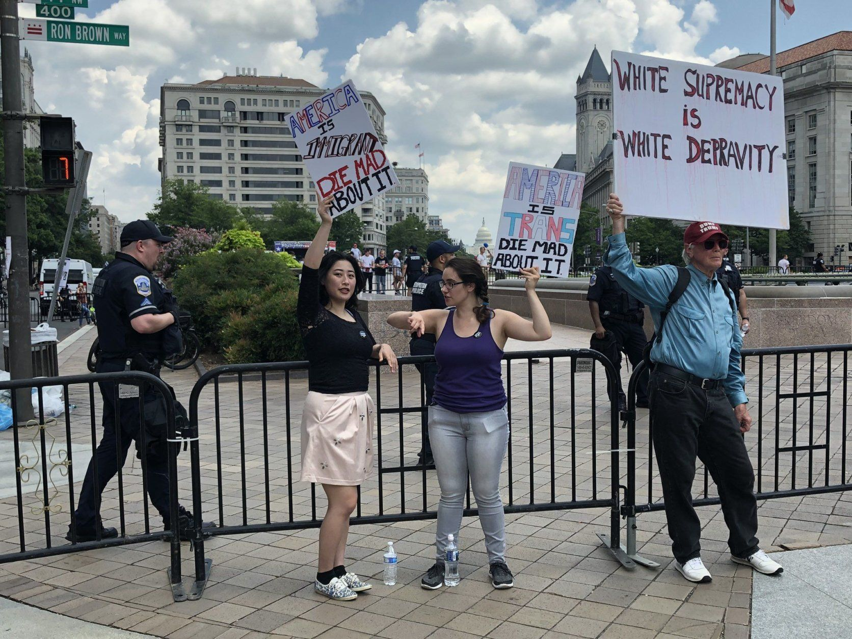 Counter protesters hold signs with Freedom Plaza behind them during demonstrations in D.C. on July 6, 2019. (WTOP/Michelle Basch)