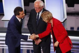 Sen. Bernie Sanders, I-Vt., watches as South Bend Mayor Pete Buttigieg shakes hands with Sen. Elizabeth Warren, D-Mass., before the first of two Democratic presidential primary debates hosted by CNN Tuesday, July 30, 2019, in the Fox Theatre in Detroit. (AP Photo/Paul Sancya)