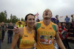 """Lithuanian couple Vytautas Kirkliauskas, right, and Neringa Kirkliauskiene celebrate their victory in the wife carrying race, a 278-yard obstacle course, during the 24th world championships in Sonkajarvi, Finland, Saturday, July 6, 2019. Despite the event's name couples don't have to be married, and organizers say male contestants could """"steal a neighbor's wife"""" if they didn't have a female companion. (AP Photo/David Keyton)"""