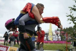 """People take part in the wife carrying race, a 278-yard obstacle course, during the 24th world championships in Sonkajarvi, Finland, Saturday, July 6, 2019. Despite the event's name couples don't have to be married, and organizers say male contestants could """"steal a neighbor's wife"""" if they didn't have a female companion. (AP Photo/David Keyton)"""
