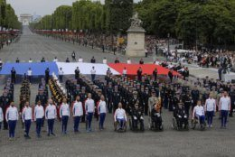 Veterans walk on the Champs-Elysees avenue during the Bastille Day parade in Paris, France, Sunday July 14, 2019. (AP Photo/Michel Euler)