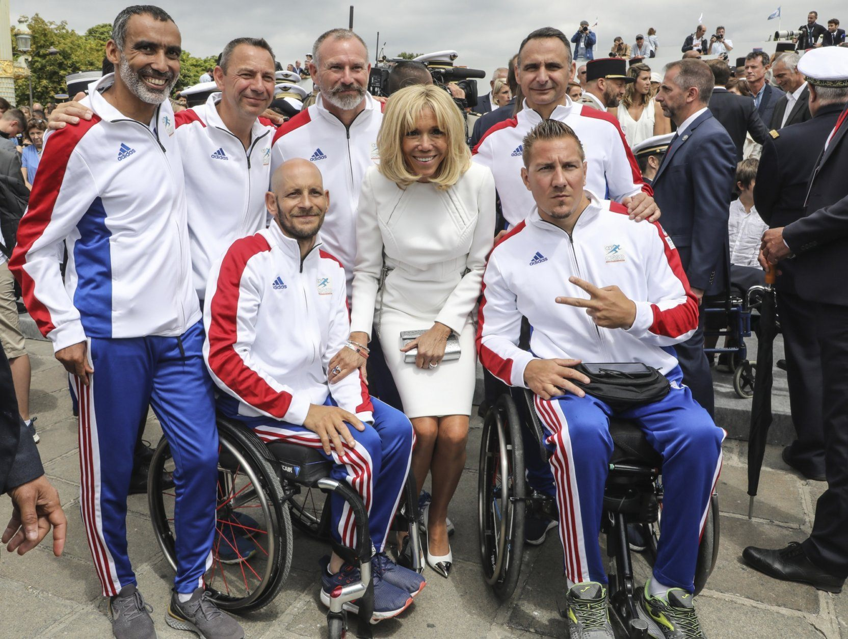 French wife's president Brigitte Macron poses with members of the French military sport's team after the annual Bastille Day military parade on the Champs-Elysees in Paris Sunday July 14, 2019. (Ludovic Marin/POOL via AP)