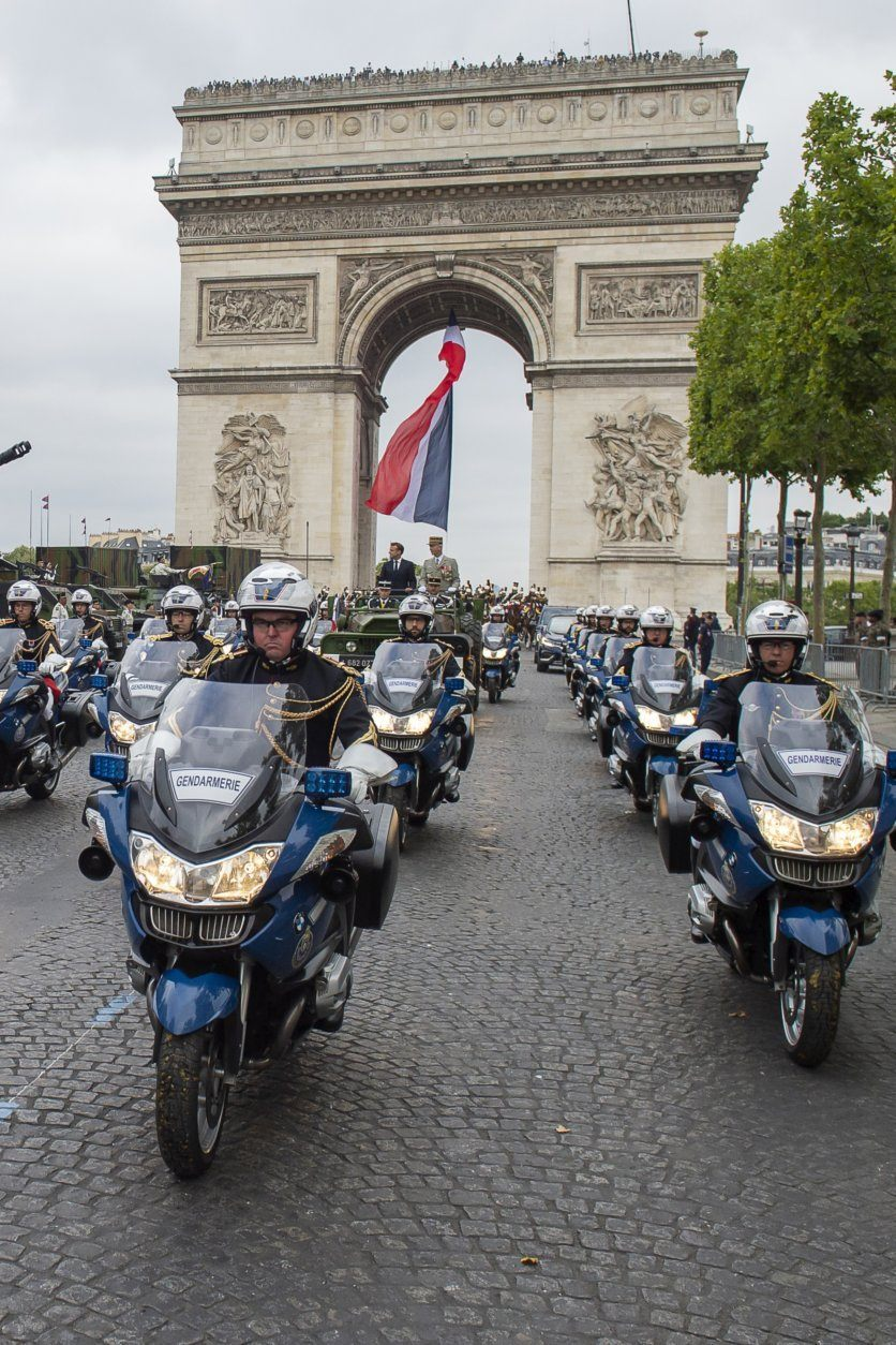 France's President Emmanuel Macron stands in his command car next to French Armies Chief Staff General Francois Lecointre as they review troops before the start of the Bastille Day military parade down the Champs-Elysees avenue in Paris Sunday, July 14, 2019. French President Emmanuel Macron has overseen France's annual Bastille Day celebration, which this year showcased European defense cooperation. ( Eliot Blondet/POOL via AP)