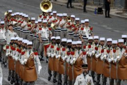 Soldiers of the Foreign legion march on the Champs-Elysees avenue during the Bastille Day parade in Paris, France, Sunday July 14, 2019. (AP Photo/Michel Euler)