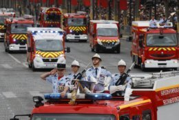Firefighters drive on the Champs-Elysees avenue during the Bastille Day parade in Paris, France, Sunday July 14, 2019. (AP Photo/Michel Euler)