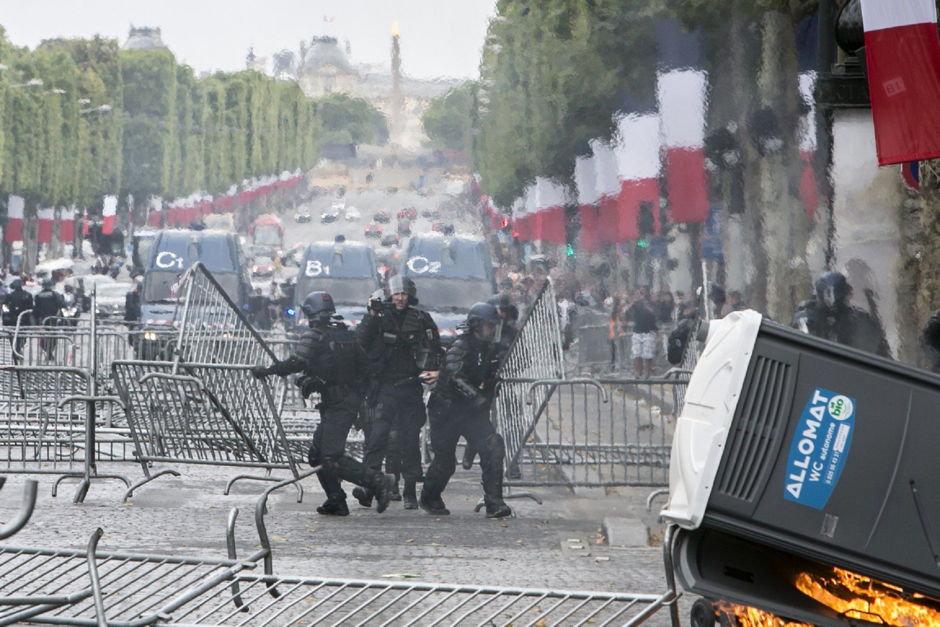 Riot police officers remove barricades that were uses as security barriers for Bastille Day parade on the Champs-Elysees avenue after scuffles with demonstrators, Sunday, July 14, 2019 in Paris. (AP Photo/Rafael Yaghobzadeh)
