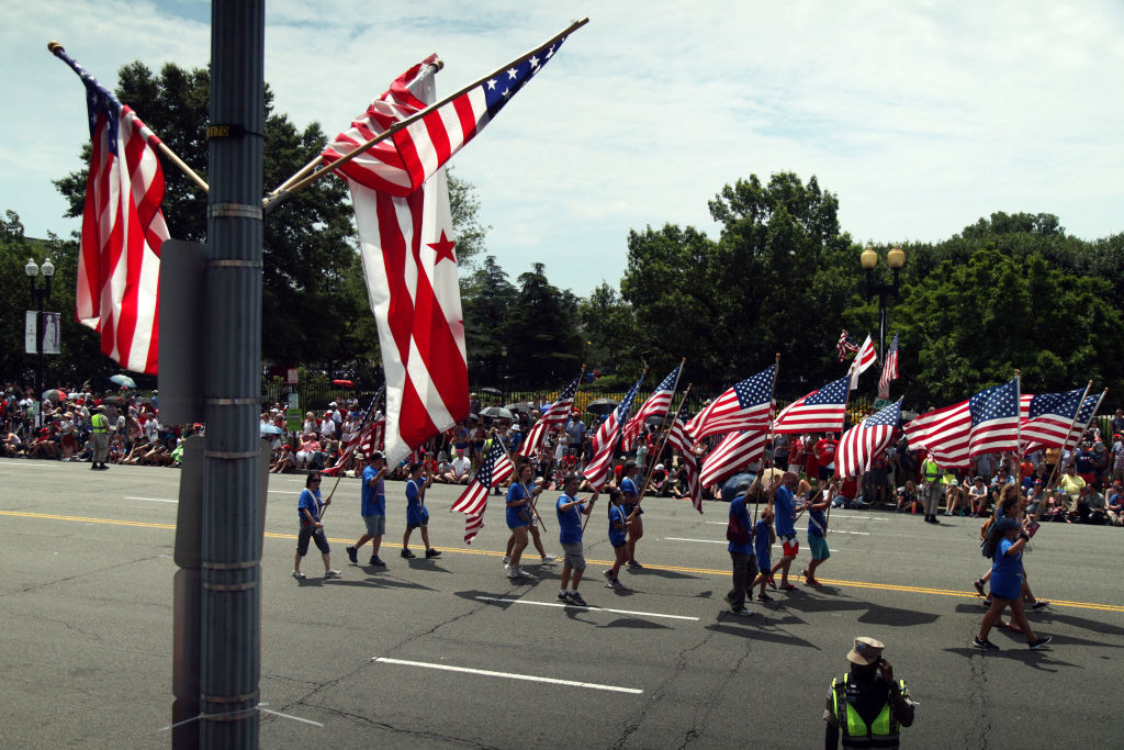WASHINGTON, DC - JULY 04: Marchers hold U.S. flags as they participate in the National Independence Day Parade July 4, 2019 in Washington, DC. Americans celebrate the nation's 243rd birthday today. (Photo by Alex Wong/Getty Images)