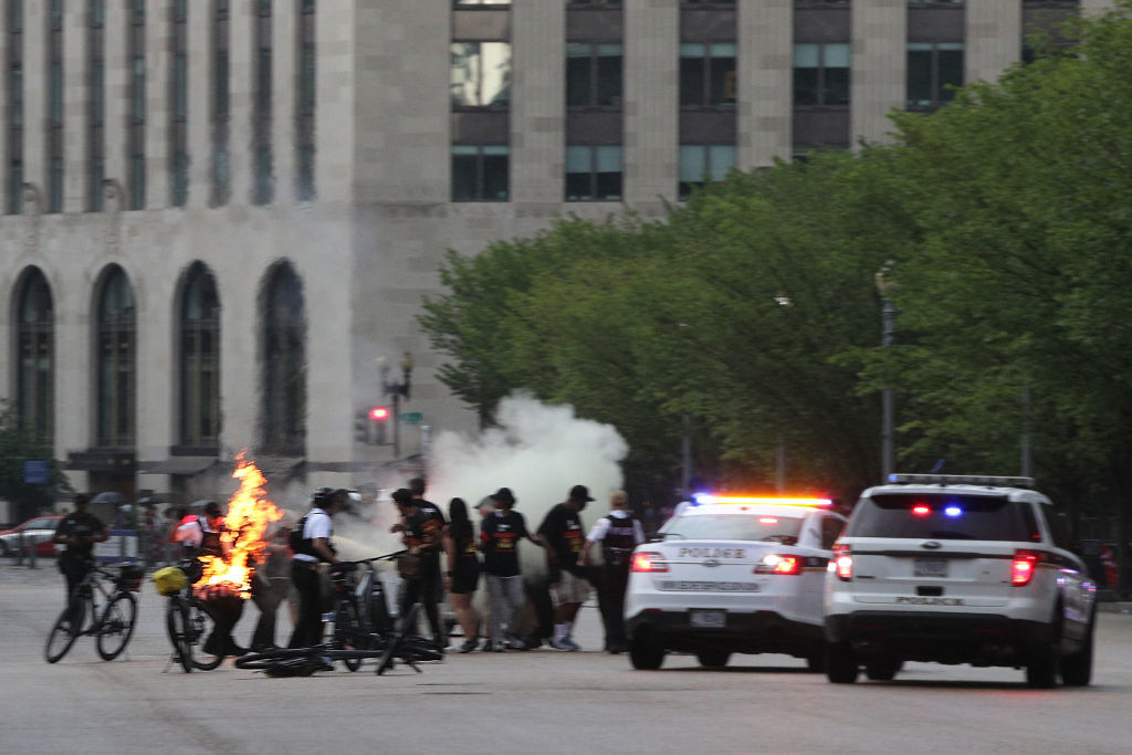 """WASHINGTON, DC - JULY 04: Members of the U.S. Secret Service try to put the fire out during an attempted flag burning on Pennsylvania Avenue in front of the White House on Independence Day July 4th, 2019 in Washington, DC. President Trump is holding a """"Salute to America"""" celebration on the National Mall on Independence Day this year with musical performances, a military flyover, and fireworks. (Photo by Alex Wong/Getty Images)"""