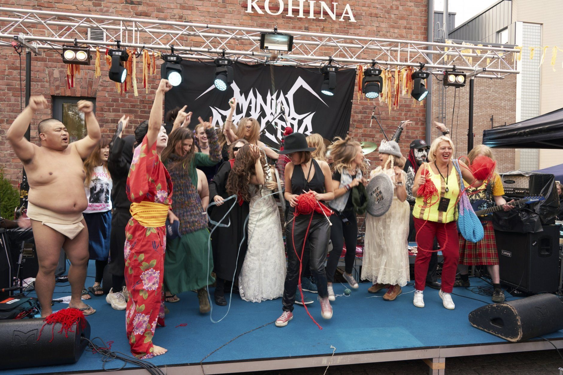 """The competitors of the first Heavy Metal Knitting world championship react on stage, Thursday, July 11, 2019 in Joensuu, Finland. With stage names such as 'Woolfumes,' 'Bunny Bandit' and '9"""" Needles,' the goal was quite simple: to showcase their knitting skills whilst dancing to heavy metal music in the most outlandish way possible. (AP Photo/David Keyton)"""