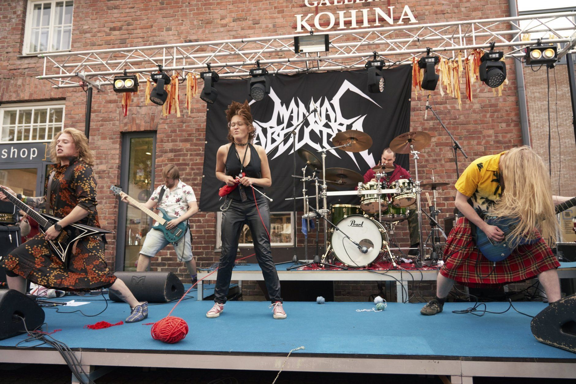"""Armed with needles and a yarn of wool, Natalia from Russia competes on stage in the heavy metal knitting world championship, Thursday, Jul. 11, 2019 in Joensuu, Finland. With stage names such as 'Woolfumes,' 'Bunny Bandit' and '9"""" Needles,' the goal was quite simple: to showcase their knitting skills whilst dancing to heavy metal music in the most outlandish way possible. (AP Photo/David Keyton)"""