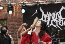 """The Japanese team Giga Body Metal react with the trophy after being crowned Heavy Metal Knitting world champions with a show featuring crazy sumo wrestlers and team-leader Manabu Kaneko dressed in a traditional Japanese kimono knitting, Thursday, July 11, 2019 in Joensuu, Finland. With stage names such as 'Woolfumes,' 'Bunny Bandit' and '9"""" Needles,' the goal was quite simple: to showcase their knitting skills whilst dancing to heavy metal music in the most outlandish way possible. (AP Photo/David Keyton)"""