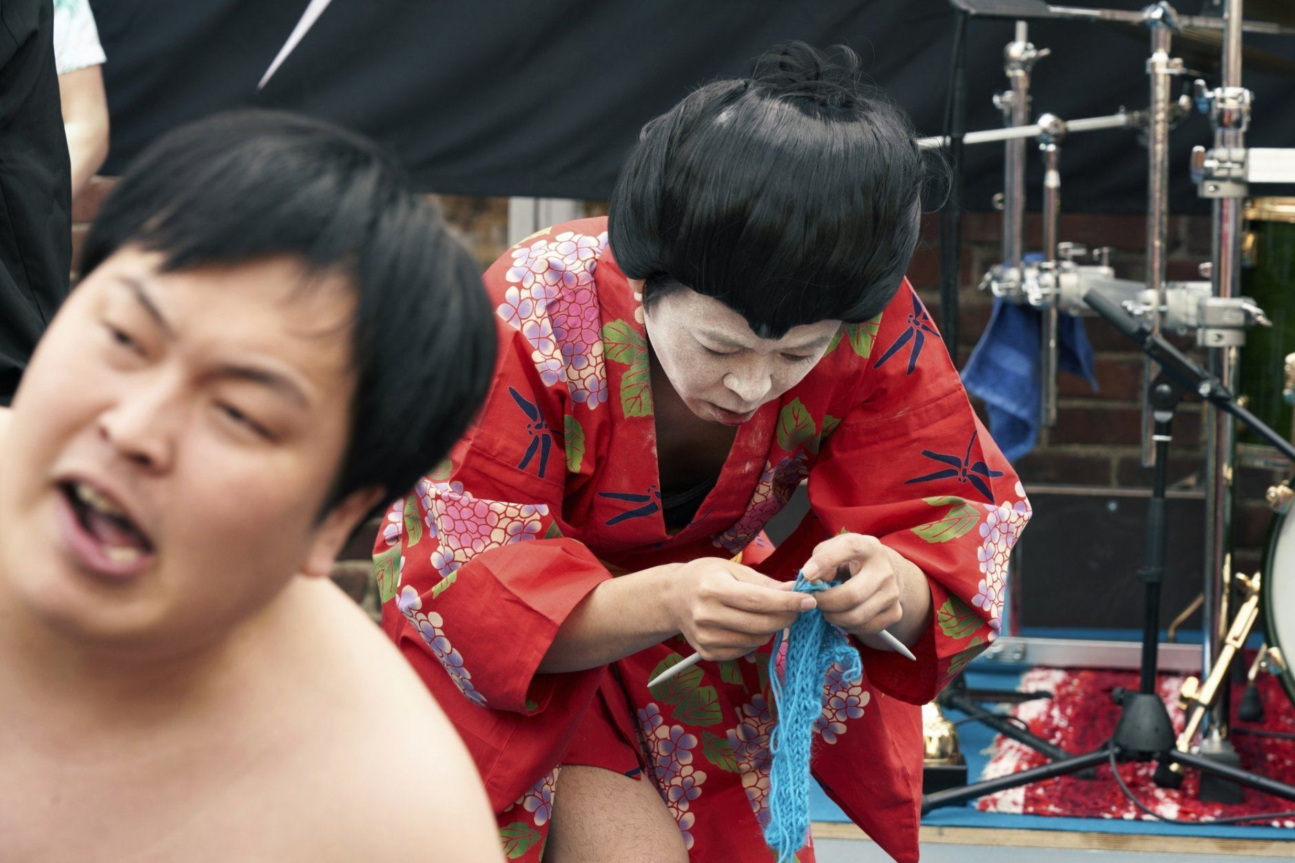 """The Japanese team Giga Body Metal perform in the Heavy Metal Knitting world champions with a show featuring crazy sumo wrestlers and team leader Manabu Kaneko dressed in a traditional Japanese kimono knitting , Thursday, July 11, 2019 in Joensuu, Finland. With stage names such as 'Woolfumes,' 'Bunny Bandit' and '9"""" Needles,' the goal was quite simple: to showcase their knitting skills whilst dancing to heavy metal music in the most outlandish way possible. (AP Photo/David Keyton)"""