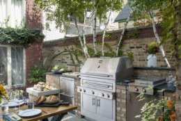 """This photo provided by Kalamazoo Outdoor Gourmet features the company's hybrid fire gas grill, refrigerated drawers and 24"""" double cooktop cabinet in an outdoor space at a home in Chicago, Ill., available from La Cuisine Appliances. As the popularity of outdoor kitchens grows, homeowners are adding outdoor ovens or heating drawer and refrigerators around their grills to prepare entire meals outside without accessing their indoor kitchen. (Kalamazoo Outdoor Gourmet via AP)"""