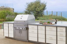This photo provided by Kalamazoo Outdoor Gourmet of it's Hybrid (charcoal, wood and gas) professional grill and Arcadia series cabinetry is shown at a home in Grand Beach, Mich. Homeowners can add a rolling cart or other freestanding item for storage and food prep space outside. But adding a built-in cooking and storage space around a grill, as seen here, increases the value of a home. (Kalamazoo Outdoor Gourmet via AP)