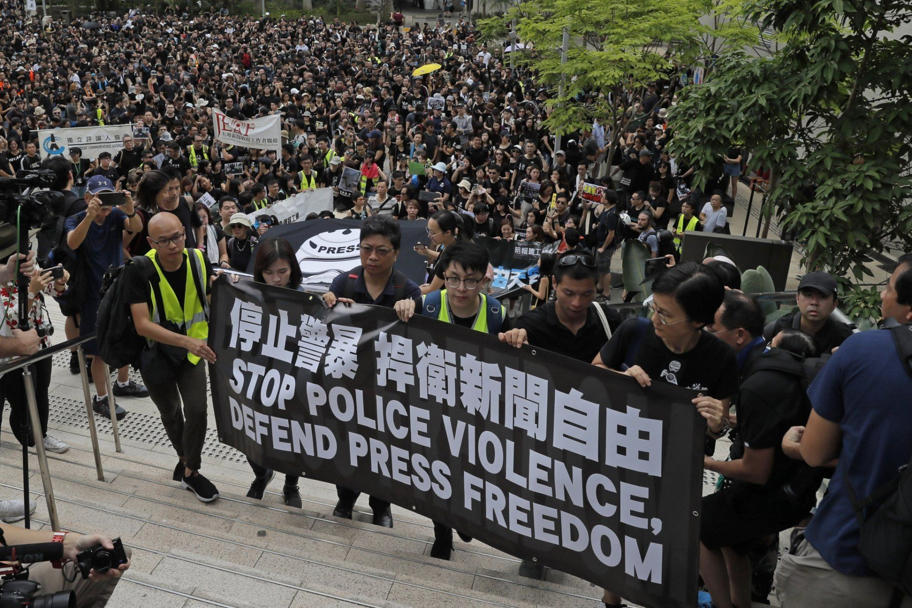 """Hundreds of journalists hold banner with words """"Stop police violence, defend press freedom"""" during a silent march to police headquarters and the government headquarters in Hong Kong, Sunday, July 14, 2019. They demand police to stop assaulting journalists and obstructing reporting. (AP Photo/Kin Cheung)"""