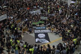 """Hundreds of journalists display banners with words """"Stop police violence, defend press freedom"""" during a silent march to police and government headquarters in Hong Kong, Sunday, July 14, 2019, demanding police to stop assaulting journalists and obstructing reporting. (AP Photo/Kin Cheung)"""