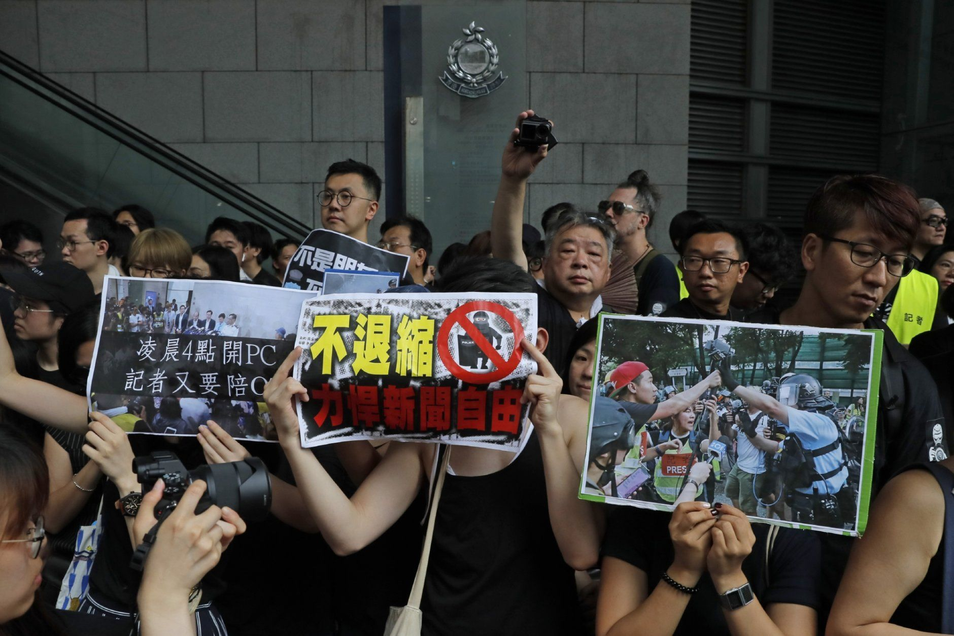 """Journalists hold placards with the words """"Not retreat, defend press freedom"""" during a silent march outside the police headquarters in Hong Kong, Sunday, July 14, 2019, demanding police to stop assaulting journalists and obstructing reporting. (AP Photo/Kin Cheung)"""