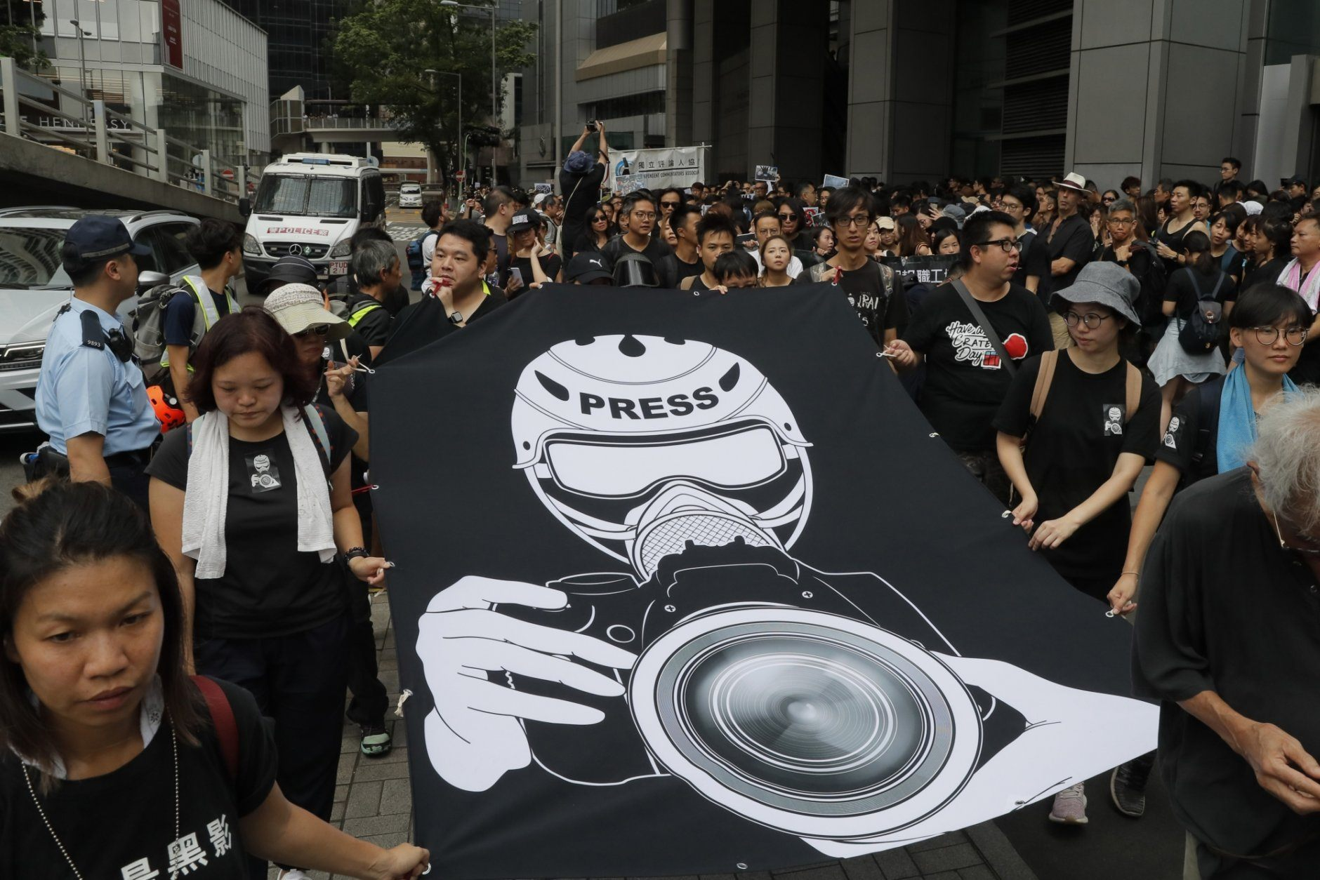 Hundreds of journalists hold banner during a silent march outside the police headquarters in Hong Kong, Sunday, July 14, 2019, demanding police to stop assaulting journalists and obstructing reporting. (AP Photo/Kin Cheung)