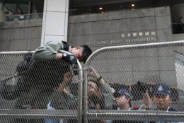 Police officers use chains to lock the barricades outside the Police Headquarters as protesters march on a street in Hong Kong, Sunday, July 21, 2019. Thousands of Hong Kong protesters marched from a public park to call for an independent investigation into police tactics. (AP Photo/Bobby Yip)