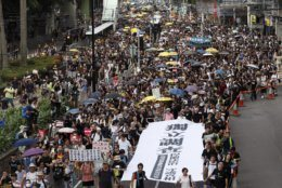 """Protesters hold a white banner reads """"""""Form an independent investigation on legislative committee"""" during a march in Hong Kong, Sunday, July 21, 2019. Thousands of Hong Kong protesters marched from a public park to call for an independent investigation into police tactics. (AP Photo/Vincent Yu)"""
