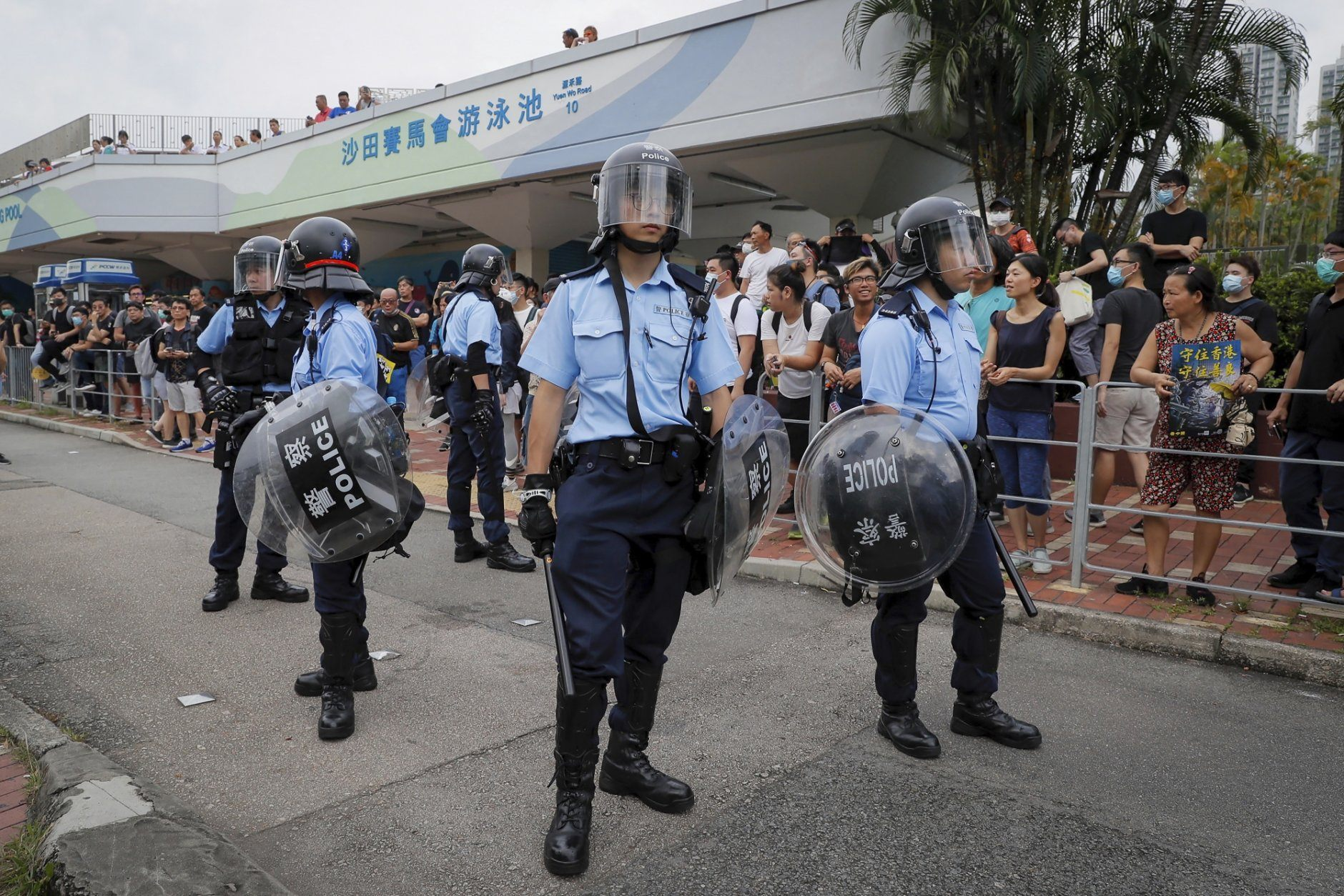 People watch policemen with shields and batons stand guard outside the Sha Tin Jockey Club Swimming Pool as thousands of protesters march through Sha Tin District in Hong Kong, Sunday, July 14, 2019. Opponents of a proposed Hong Kong extradition law have begun a protest march, adding to an outpouring of complaints the territory's pro-Beijing government is eroding its freedoms and autonomy.