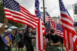 A protester, center right, holds U.S. flags with others and sings U.S. national anthem as they take part in a march at Victoria Park in Hong Kong, Sunday, July 21, 2019. Thousands of Hong Kong protesters marched from a public park to call for an independent investigation into police tactics.(AP Photo/Vincent Yu)