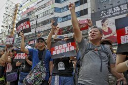 """Protesters gesture while holding placards reads """"Form an independent investigation on legislative committee"""" during a march in Hong Kong, Sunday, July 21, 2019. Thousands of Hong Kong protesters marched from a public park to call for an independent investigation into police tactics.(AP Photo/Vincent Yu)"""