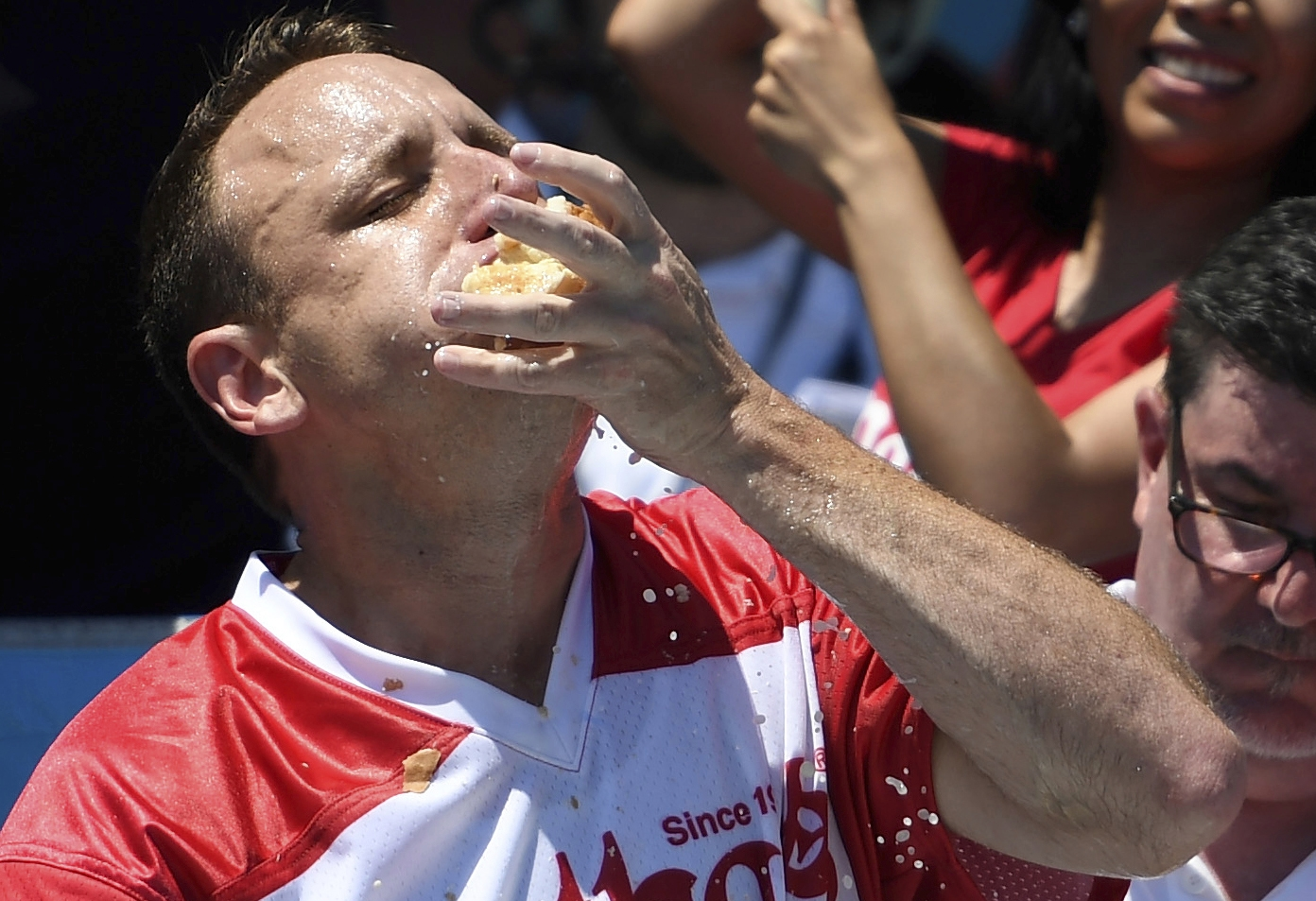 Joey Chestnut stuffs his mouth with hot dogs during the men's competition of Nathan's Famous July Fourth hot dog eating contest, Thursday, July 4, 2019, in New York's Coney Island. (AP Photo/Sarah Stier)