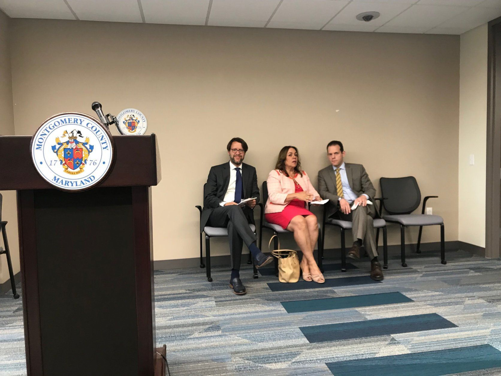 County council member Hans Reimer, Council President Nancy Navarro and Council Member Evan Glass prepare to speak at the meeting. (WTOP/Dick Uliano)
