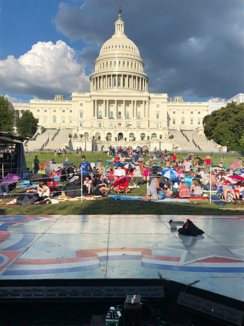 People gather on the West Lawn for the concert's full dress rehearsal Wednesday night. (WTOP/Michelle Basch)