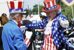 Uncle Sams Fred Polnisch and Gordon Dunham greet each other before the Fourth of July Parade, Thursday July 4, 2019, in the Pittsfield, Mass. (Ben Garver/The Berkshire Eagle via AP)