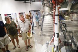 Visitors look onto a scale model of the Saturn V rocket used in the United State's Apollo program at the Armstrong Air & Space Museum as special events are underway for visitors commemorating the 50th anniversary of the first moon landing, Saturday, July 20, 2019, in Wapakoneta, Ohio. (AP Photo/John Minchillo)