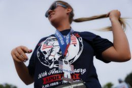 """A runner receives her medal after participating in the """"Run for the Moon"""" race outside the Armstrong Air & Space Museum as special events are underway for visitors commemorating the 50th anniversary of the first moon landing, Saturday, July 20, 2019, in Wapakoneta, Ohio. (AP Photo/John Minchillo)"""
