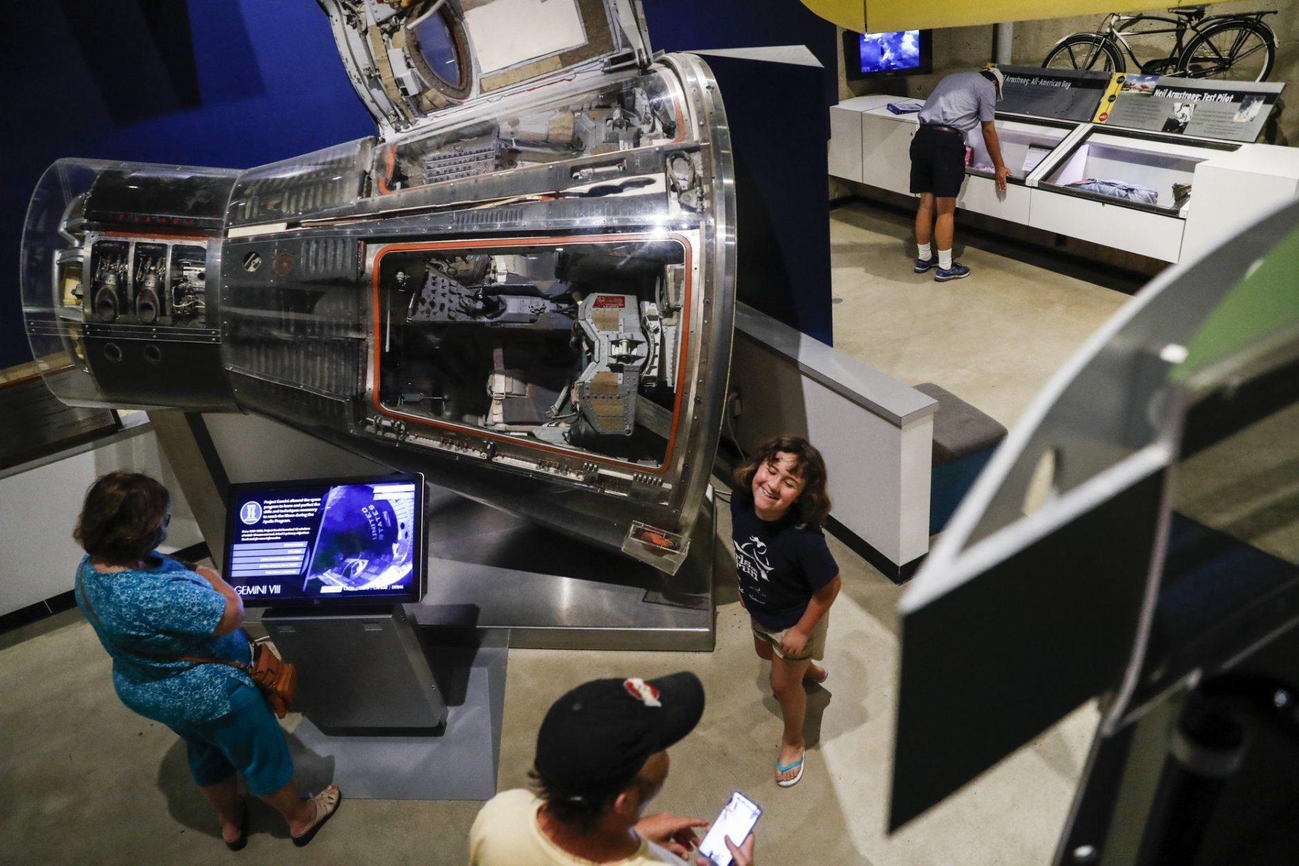 Visitors browse an exhibit featuring the Gemini VIII spacecraft at the Armstrong Air & Space Museum, Wednesday, June 26, 2019, in Wapakoneta, Ohio.  Neil Armstrong helped put Wapakoneta  on the map July 20, 1969, when he became the first human to walk on the moon. The late astronaut remains larger than life in the city 60 miles (96.56 kilometers) north of Dayton, where visitors are greeted by the space base-shaped top of the space museum named for him as they exit Interstate 75. (AP Photo/John Minchillo)