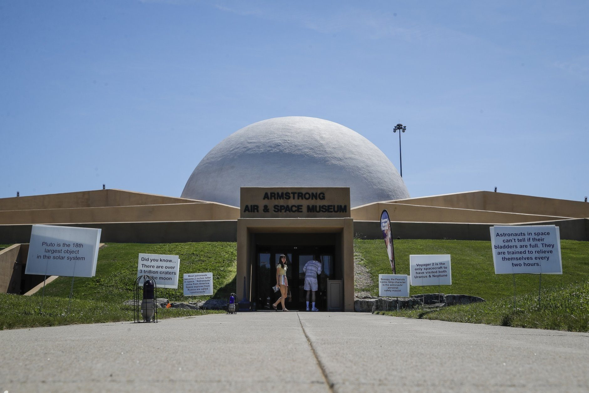 Visitors linger outside the Armstrong Air & Space Museum, Wednesday, June 26, 2019, in Wapakoneta, Ohio.  Neil Armstrong helped put Wapakoneta  on the map July 20, 1969, when he became the first human to walk on the moon. The late astronaut remains larger than life in the city 60 miles (96.56 kilometers) north of Dayton, where visitors are greeted by the space base-shaped top of the space museum named for him as they exit Interstate 75.  (AP Photo/John Minchillo)