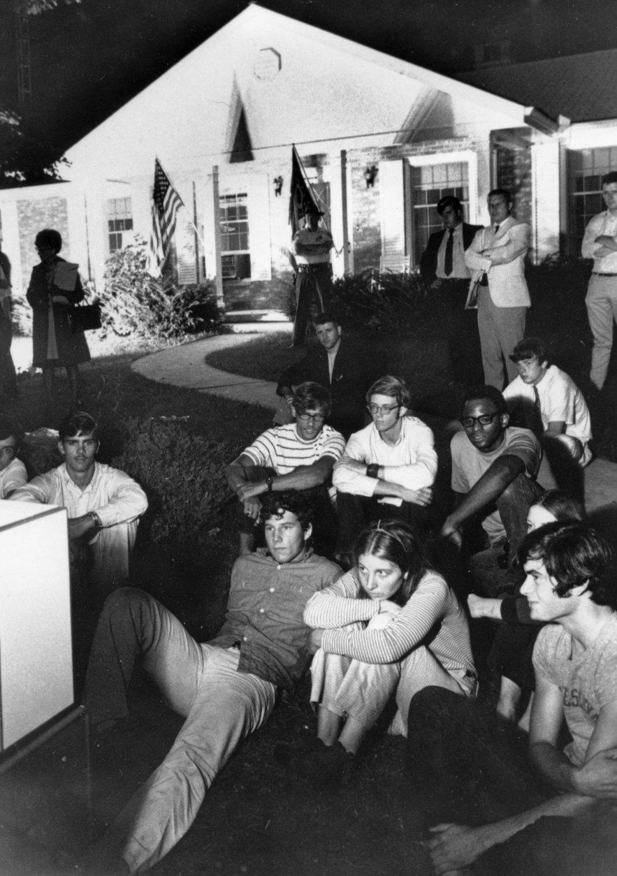 FILE - In this July 20, 1969 file photo, people sit on the lawn of the home of Stephen Armstrong in Wapakoneta, Ohio, to watch astronaut Neil Armstrong walk on the moon. Neil Armstrong helped put Wapakoneta  on the map July 20, 1969, when he became the first human to walk on the moon. The late astronaut remains larger than life in the city 60 miles (96.56 kilometers) north of Dayton, where visitors are greeted by the space base-shaped top of the space museum named for him as they exit Interstate 75.  (AP Photo/Bill Sauro)
