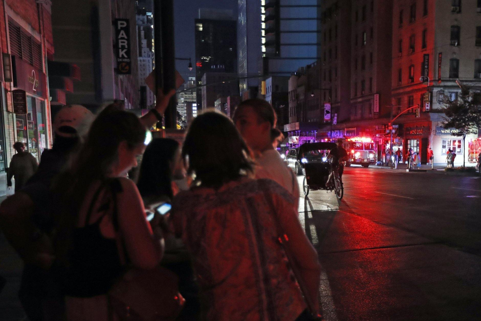 People gather in midtown Manhattan during a widespread power outage, Saturday, July 13, 2019, in New York. Authorities were scrambling to restore electricity to Manhattan following a power outage that knocked out Times Square's towering electronic screens, darkened marquees in the theater district and left businesses without electricity, elevators stuck and subway cars stalled. (AP Photo/Michael Owens)